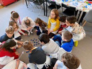 A képen a gyerekek próbálják megoldani a feladványt, hogy senki ne változzon békává.