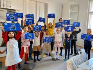 Az elkészült festményeket mutatják büszkén a gyerekek.