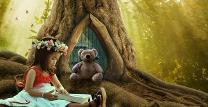 A képen egy gyönyörűkislány olvas az erdőben, fején virágkoszorú, mellette a macija hallgatja
