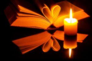 A gyertyafényes képen egy nyitott könyv látható, melnyek néhány lapját szív alakot formázva visszahajtották.