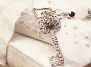 A képen egy gönggyel díszatett gyönyörű kulcs látható néhány könyvre helyezve