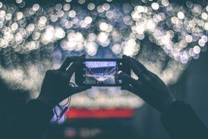 Egy kézpár egy telefont fényképezésre emel, míg a háttérben a vizen megtörő fénycseppek szikráznak