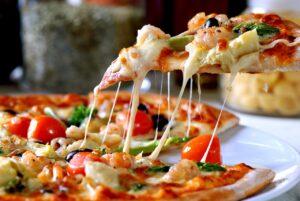 A képen egy olvadt sajttól roskadozó pizzaszelet látható