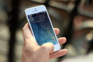 A képen egy mobiltelefont felemelő női kéz látható